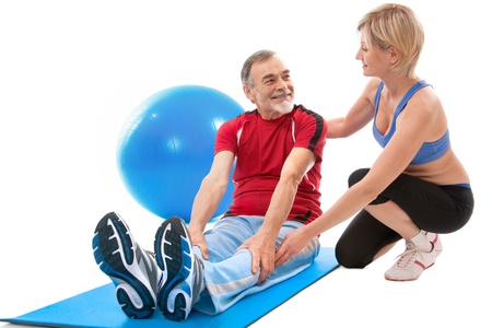 Senior man doing fitness exercise with help of trainer at sport gym photo