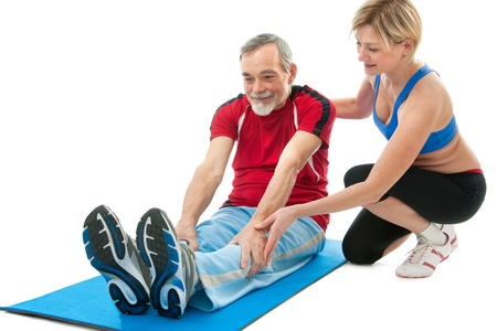 strength therapy: Senior man doing fitness exercise with help of trainer at sport gym