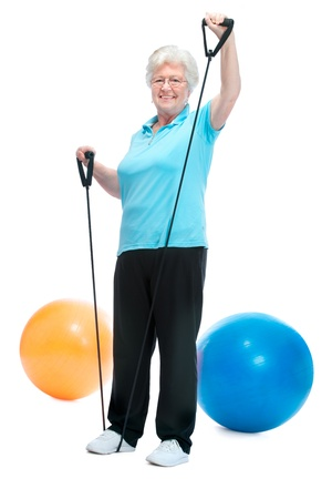 Attractive senior woman at health club, doing exercises with a chest expander Stock Photo - 13336384