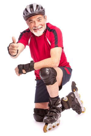 senior man goes inline skating and shows thumbs up Stock Photo - 13336417
