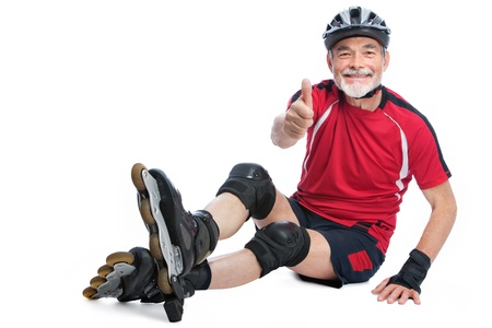 senior man goes inline skating and shows thumbs up photo