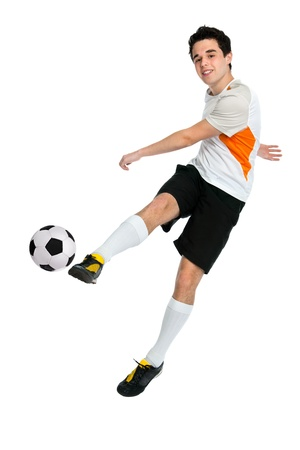 soccer kick: soccer player shooting a ball isolated on white background