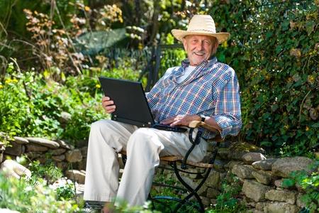 senior ordinateur: Vieil homme utilisant un ordinateur portable dans le parc