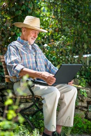 active retirement: Elderly man using laptop in the park
