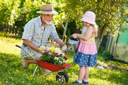 family gardening: Happy grandfather with his granddaughter pouring flowers in the garden