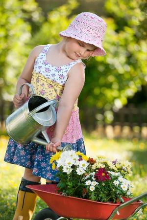 Niños ayudando: La niña vertiendo flores en el jardín