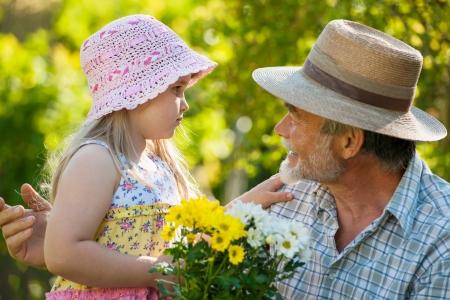 Gelukkig opa met zijn kleindochter in de tuin