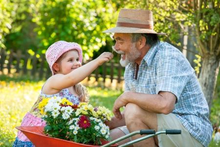 Feliz abuelo con su nieta en el jardín