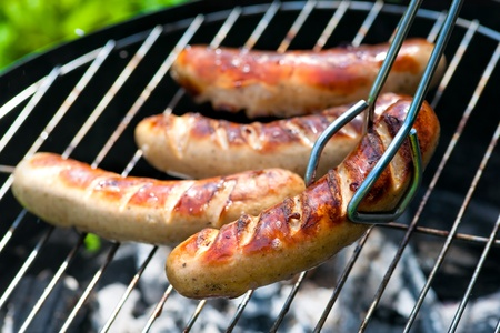 Delicious german sausages on the barbecue grill photo