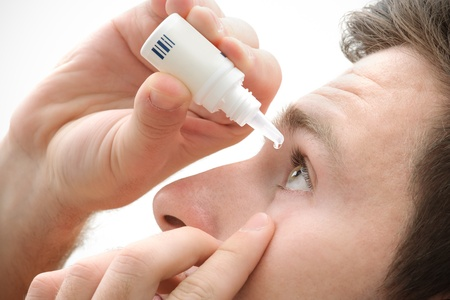 Closeup view of young man applying eye drop photo