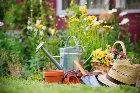 flower basket: Gardening tools and a straw hat on the grass in the garden Stock Photo