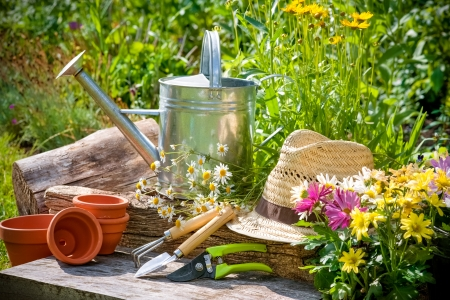 Gardening tools and a straw hat on the grass in the garden Stock Photo