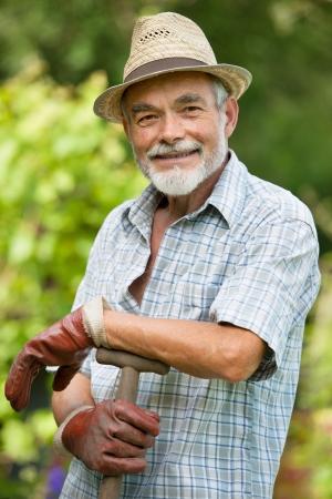 Senior gardener with a spade in the garden photo