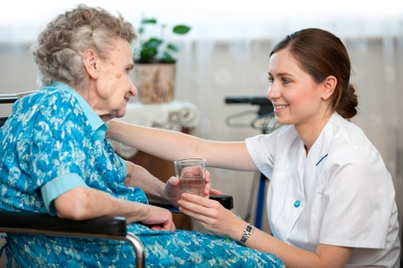 medical help: Senior woman with her caregiver at home Stock Photo