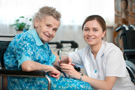 elderly hands: Senior woman with her caregiver at home Stock Photo