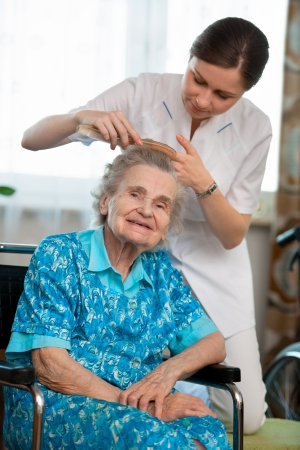 nursing young: Nurse dressing the hair of a senior woman