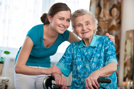 old age care: Senior woman with her caregiver at home Stock Photo