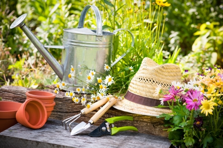 watering can: Gardening tools and a straw hat on the grass in the garden Stock Photo