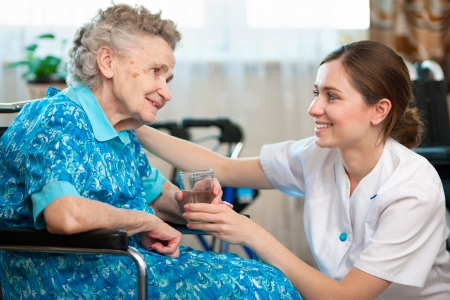 care at home: Senior woman with her caregiver at home Stock Photo