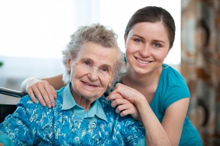 vejez feliz: Mujer mayor con su cuidador en el hogar