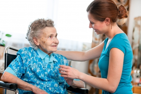 assistance: Senior woman with her caregiver at home Stock Photo