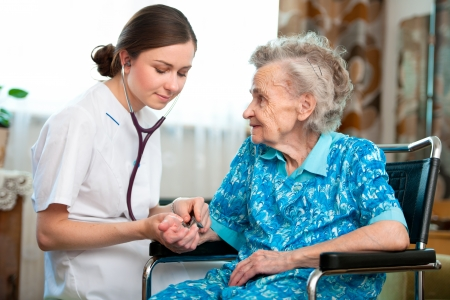 Senior woman with her caregiver at home Stock Photo - 14456386
