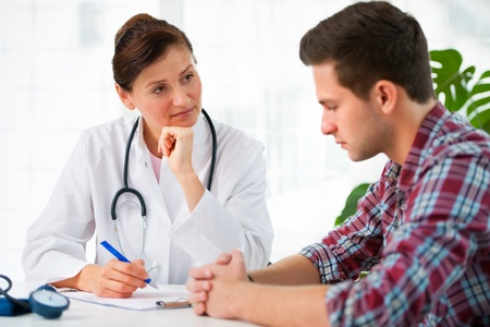 visit: doctor talking to her male patient at office