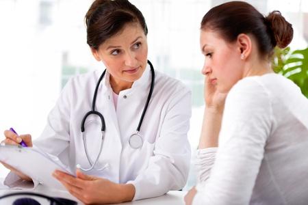 medico la diagnosi spiegando al suo paziente di sesso femminile Archivio Fotografico