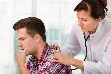 öksürük: kadın doktor genç bir adam soğuk algınlığı inceliyor