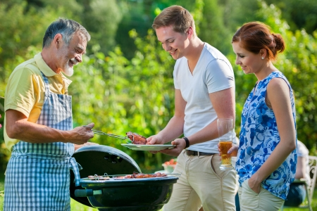 family garden: Family having a barbecue party in their garden in summer