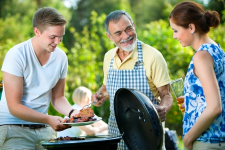 hot grill: Family having a barbecue party in their garden in summer