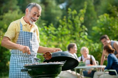 carne asada: Familia tener una barbacoa en el jard�n en verano Foto de archivo