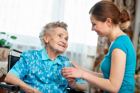 Senior woman with her caregiver at home Stock Photo