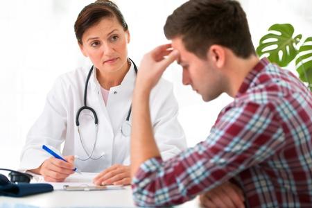 hoofdpijn: arts te praten met haar mannelijke patiënt op het kantoor van Stockfoto