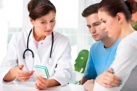 醫療保健: 女醫生提供醫療建議,以一對年輕夫婦在辦公室 版權商用圖片