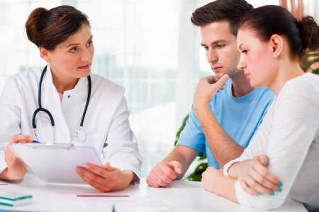 pacientes: doctora ofrecer consejos médicos a una joven pareja en la oficina