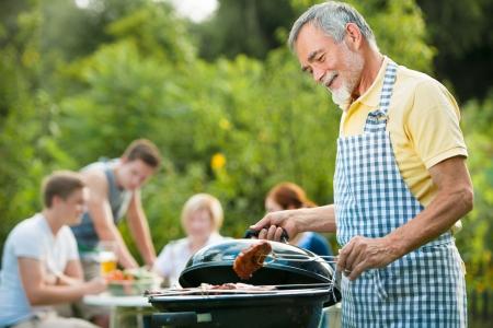 fiesta familiar: Familia tener una barbacoa en el jard�n en verano Foto de archivo