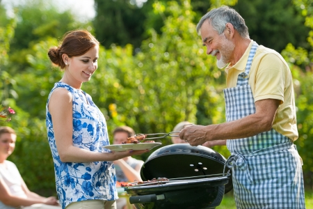 grandfather: Family having a barbecue party in their garden in summer