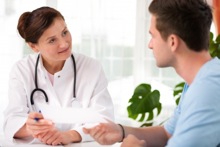 doctor talking to her male patient at office photo