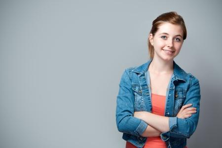 adolescentes estudiando: posici�n, sonriente adolescente con los brazos cruzados Foto de archivo