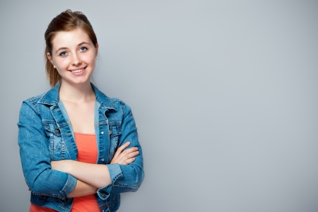 smiling teenage girl standing with crossed arms photo