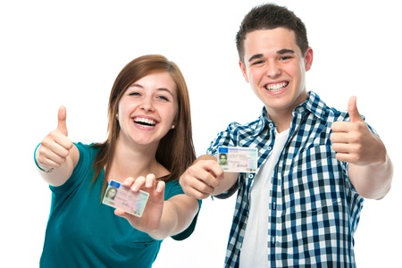 happy teens showing their driving license photo