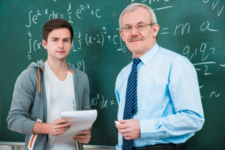 secondary education: male student with a teacher in classroom