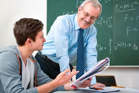 maestra ense�ando: estudiante masculino con un profesor en el aula Foto de archivo