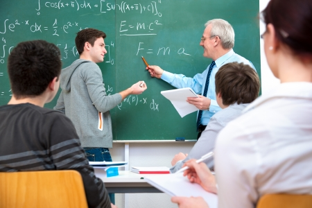high school: Teacher with a group of high school students in classroom Stock Photo