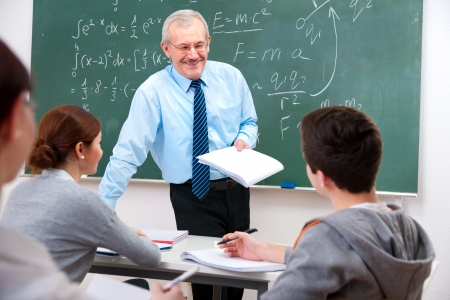 secondary schools: Teacher with a group of high school students in classroom Stock Photo