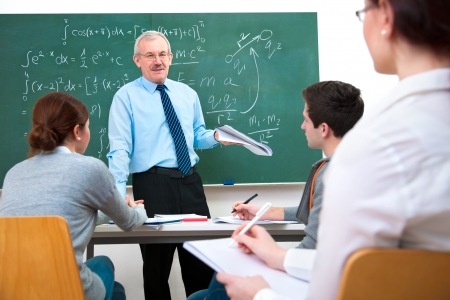 high school students: Teacher with a group of high school students in classroom Stock Photo