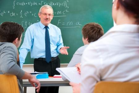 教師: 老師帶了一群高中生在教室 版權商用圖片