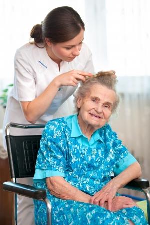 peine: Enfermera vestirse el cabello de una mujer mayor