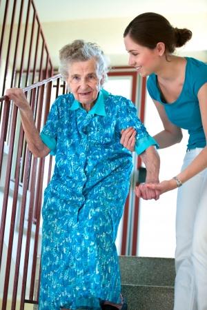 ヘルスケア: 年配の女性は介護者と階段を登る 写真素材